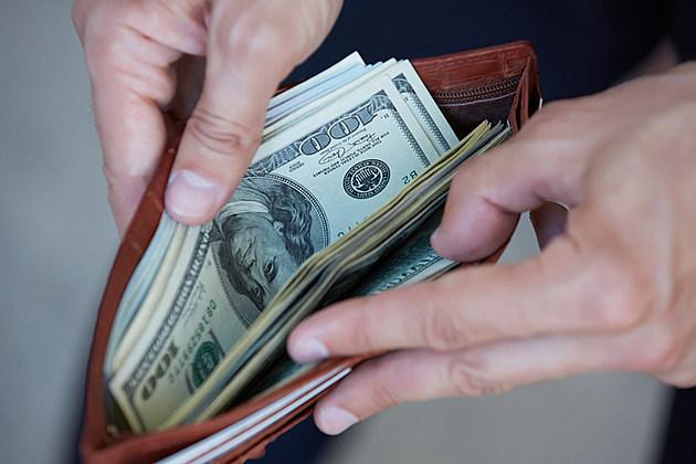 man holding a purse with money closeup